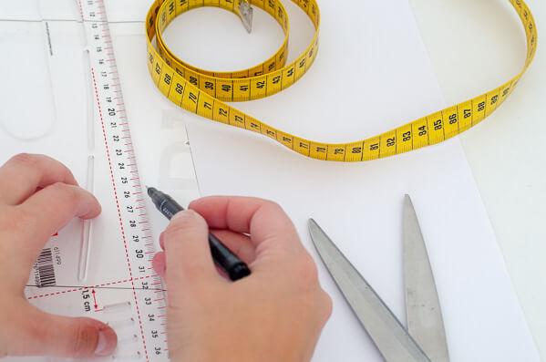 Schnittmuster erstellen und anpassen. Zwei Hände, die an einem Kurvenlineal zeichnen, daneben ein Maßband und eine Stoffschwere.