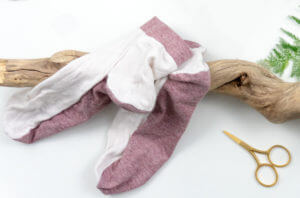 Selbstgenähte Socken in rosa auf schönem Dekoast und kleiner goldener Schere