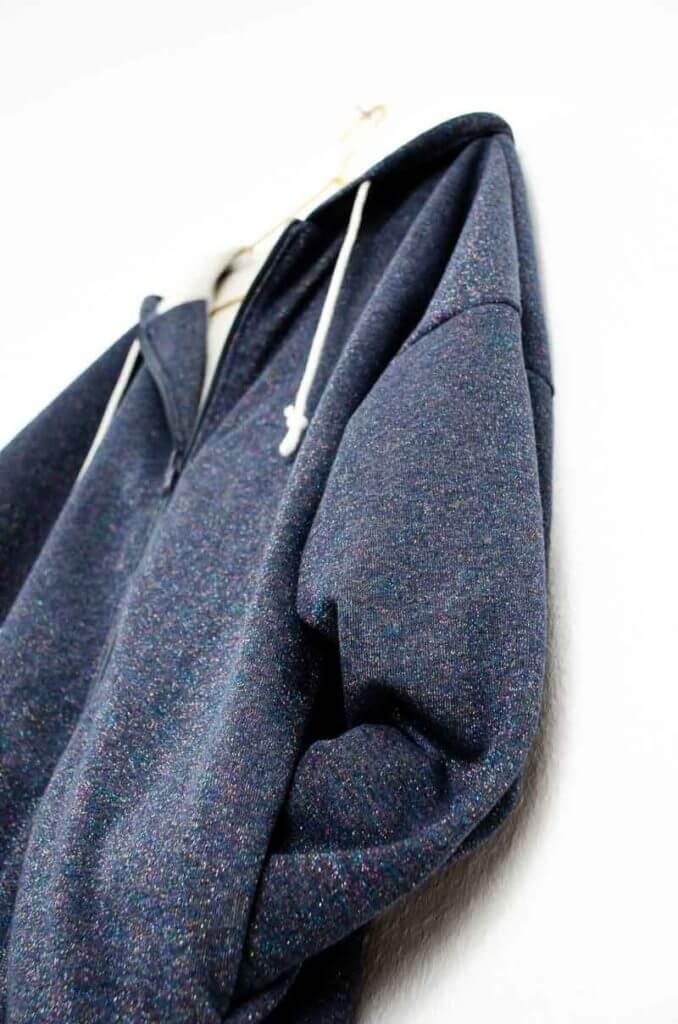 Seitliche Eingrifftasche. Detail dunkelblaue Sweatjacke.