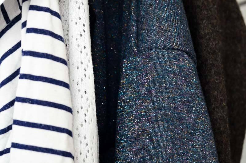DIY Capsule Wardrobe. Wenige Kleidungsstücke farblich abgestimmt auf Garderobenständer in Detailaufnahme.