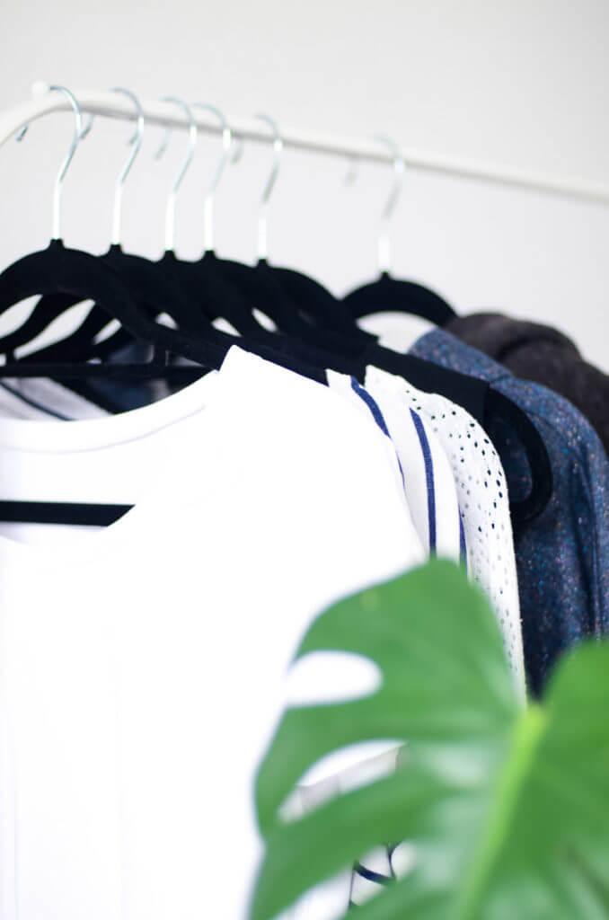 DIY Capsule Wardrobe. Wenige Kleidungsstücke farblich abgestimmt auf Garderobenständer mit Pflanze im Vordergrund.