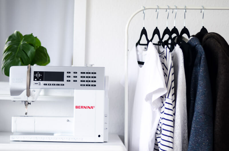 DIY Capsule Wardrobe. Wenige Kleidungsstücke farblich abgestimmt auf Garderobenständer, daneben eine Nähmaschine.